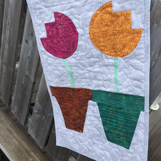 Quilted wall hanging with four tulips each in a flower pot. Northcott Artisan Spirit Shimmer Echoes.