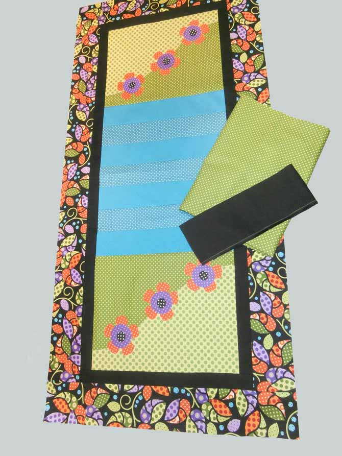The landscape table runner with a piece of green polka dot fabric selected for the backing, and a piece of solid black fabric selected for the binding. Northcott Urban Elementz.