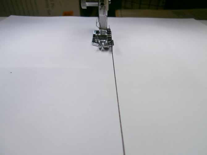 """The guide on the ¼"""" quilting foot is aligned with the line on the paper"""