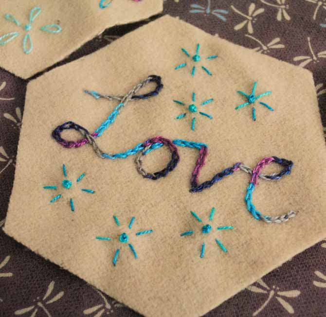 Chain-stitched words on the wool hexagons
