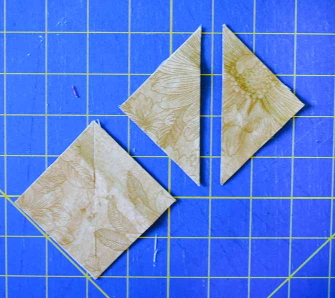 Here on the cutting mat are the smaller beige triangles which have been cut diagonally once to make the smaller setting triangles.