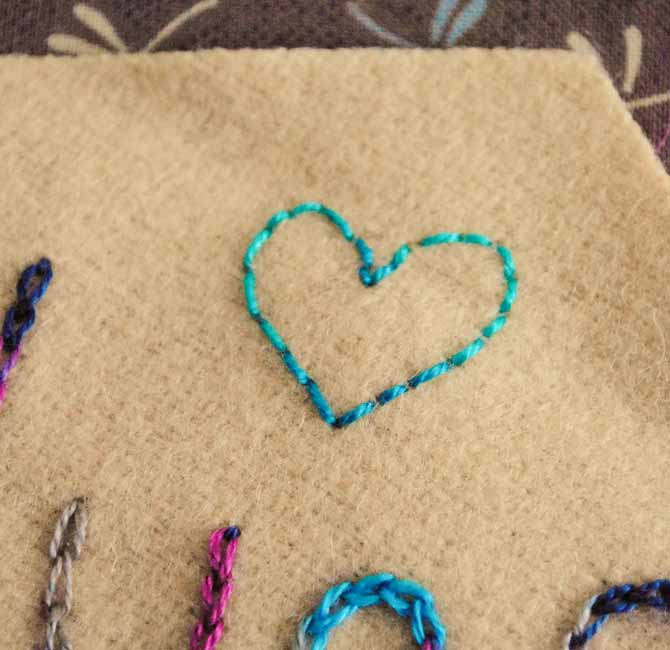 Back stitching is used to stitch a heart on one of the wool hexagons