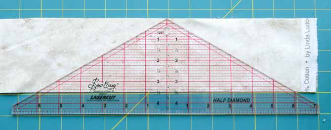 The Sew Easy Half Diamond ruler is placed on fabric for cutting.
