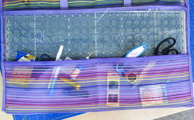 6 ½″ x 24″ ruler sliding into the clear zippered pocket of the purple mesh sunshine mat tote on a blue Unique mat