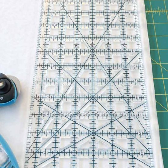 Align the TrueCut ruler to the edge of the fabric.