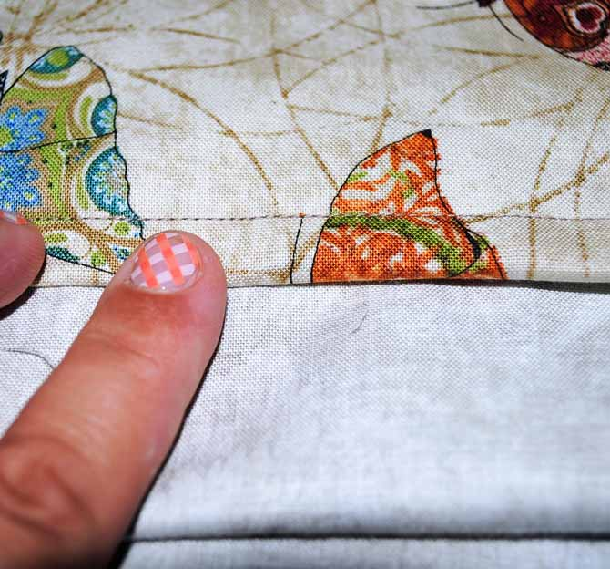 On the inside of the pillowcase, the extra cuff fabric that extends past this seam is folded over the raw edges and pinned in place.