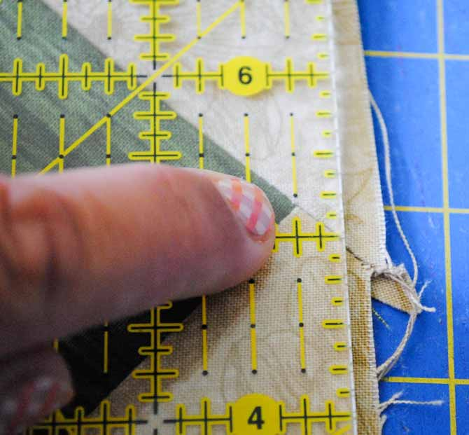 "This picture shows the rotary cutting ruler lined up on the border ¼"" away from the points of the squares."