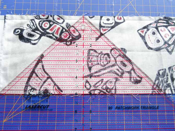 """Align the 5"""" line of the ruler to the edge of the fabric."""