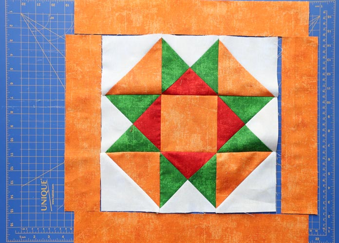 Quilt block layout with orange lattice and orange center block.