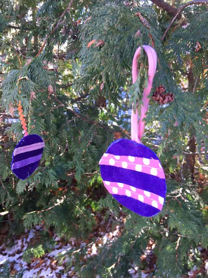 Two tree ornaments in the shape of balls hanging from cedar trees.