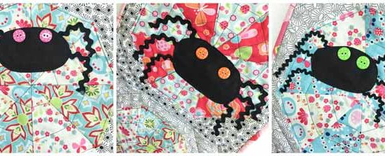 3 black fabric spiders with polka dot button eyes on a quilt.