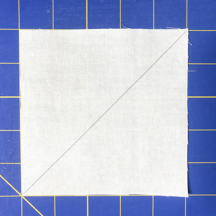 "Make diagonal line on the back of every 5"" X 5"" square of the cream-colored fabric."