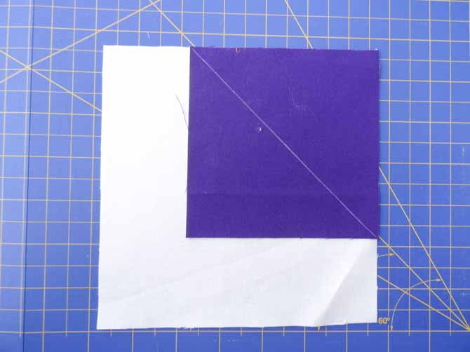 Place colored fabric on the upper right corner of the white fabric square.