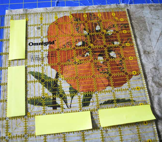 "A large square ruler with sticky notes stuck to it, to show the 7"" square for fussy cutting."