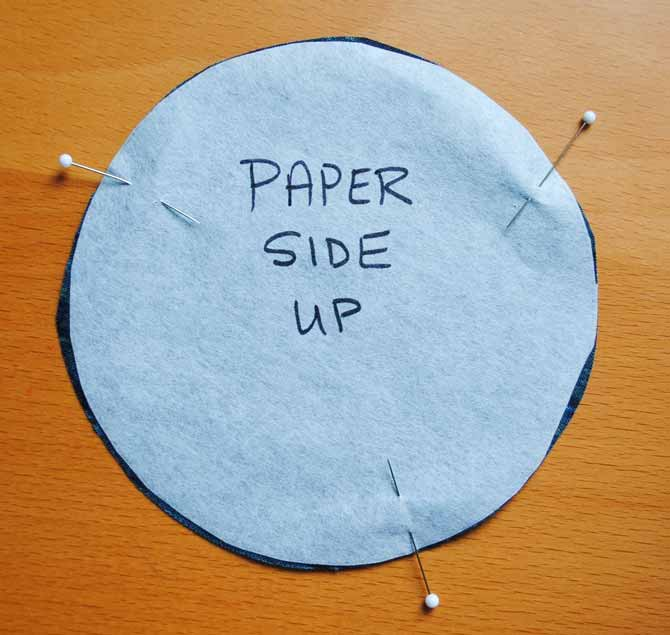 Layer the interfacing and the fabric circle so that the right side of the fabric is facing the adhesive side of the interfacing