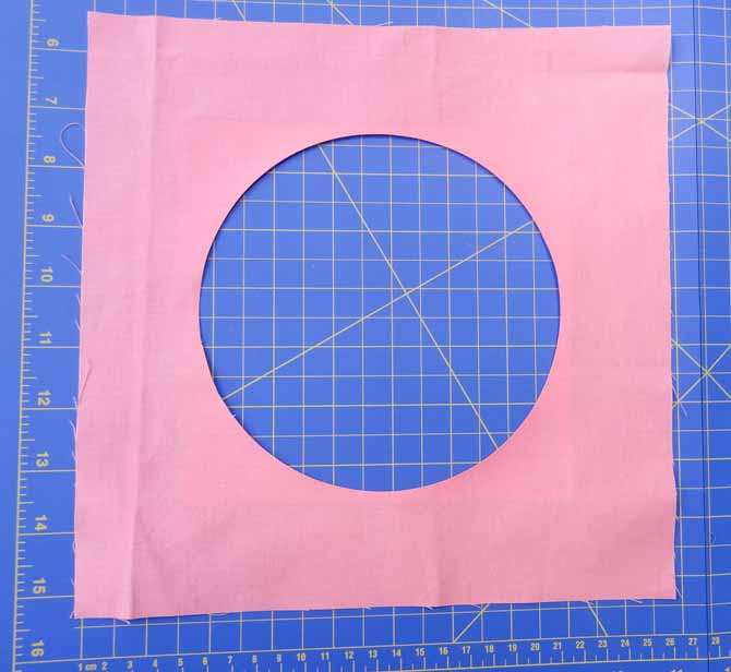 A prefect centered circle is cut from one of the fabric squares.