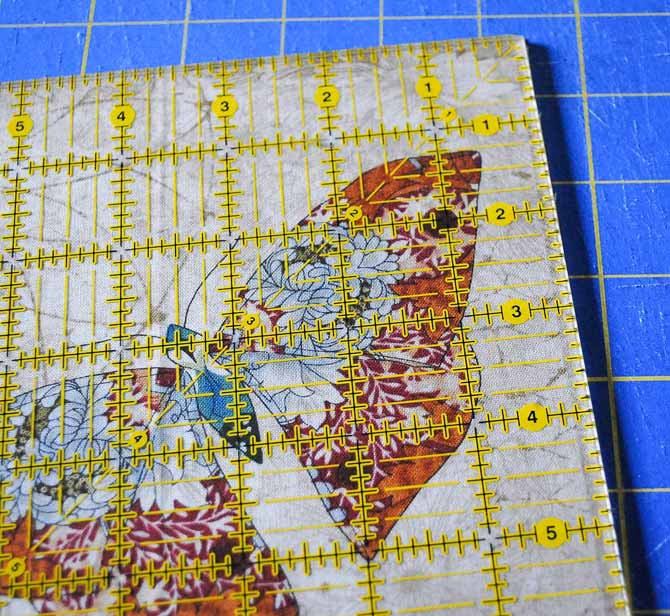 A rotary cutter and ruler on the fabric square showing how to trim the top and left side of the square first