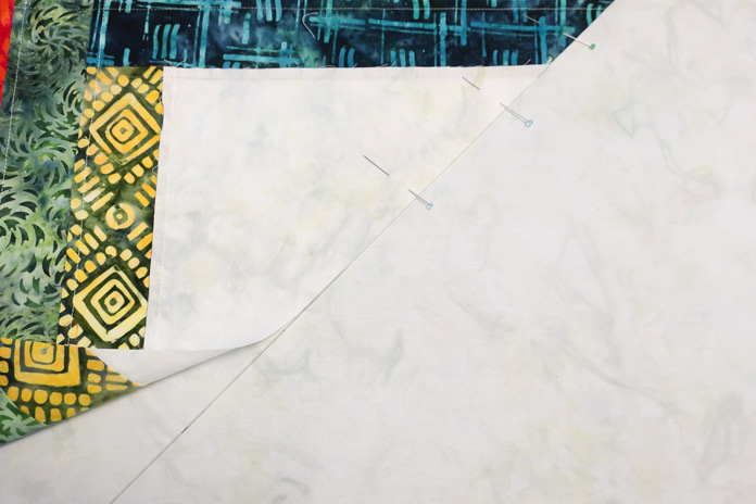 Align the diagonal half block edge with the line drawn on the background fabric.