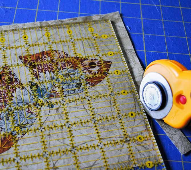 A rotary cutter and ruler trimming off the remaining two edges of the fabric square after it has been rotated.