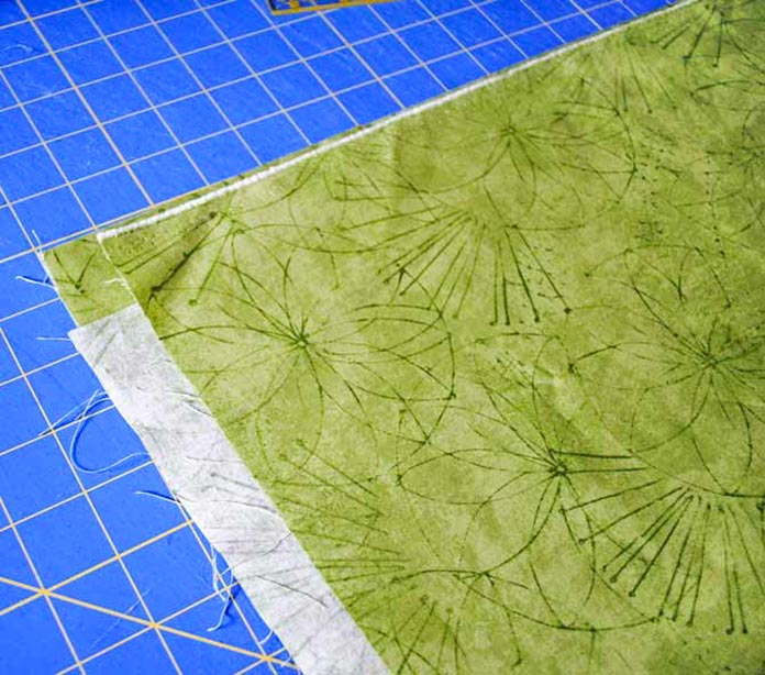 Fold the fabric in half twice, aligning the other folded edge and the selvages