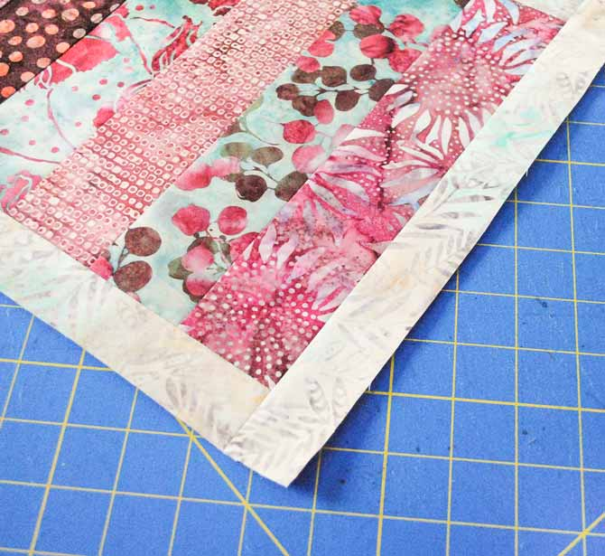 The inner border strips are sewn first to the long edges of the table runner, then to the short edges
