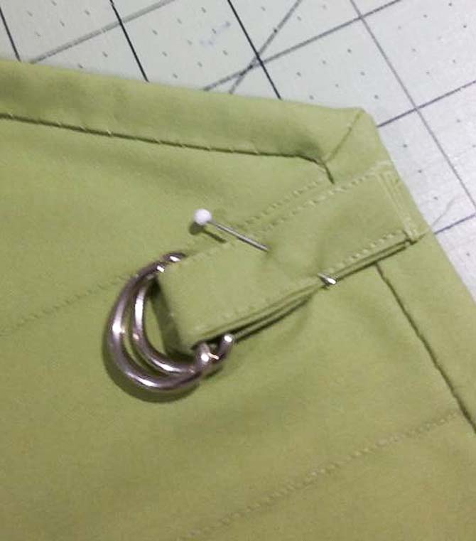 The small strap made with Northcott Colorworks solid fabric and D-rings is pinned to the neck of the apron panel prior to sewing.