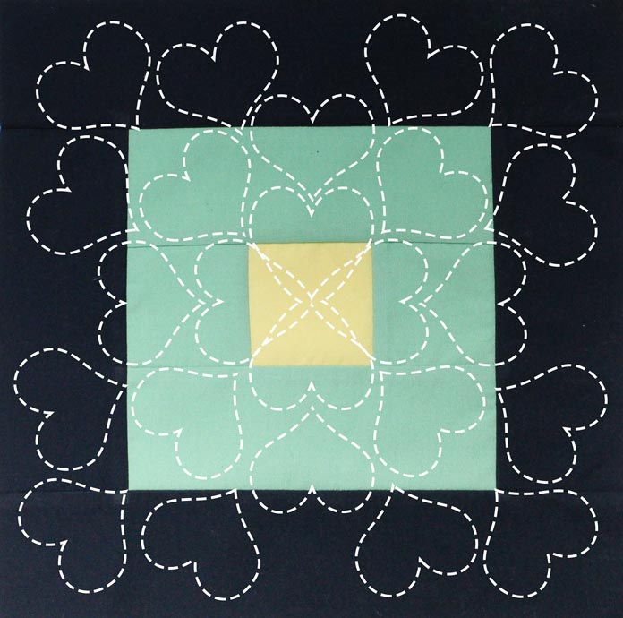 Free-motion heart quilting wreath is my idea for the blocks