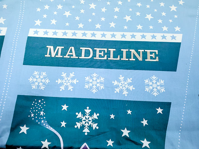 Embroidered name Madeline on Christmas fabric using the Husqvarna Viking Designer Brilliance 80 sewing and embroidery machine.