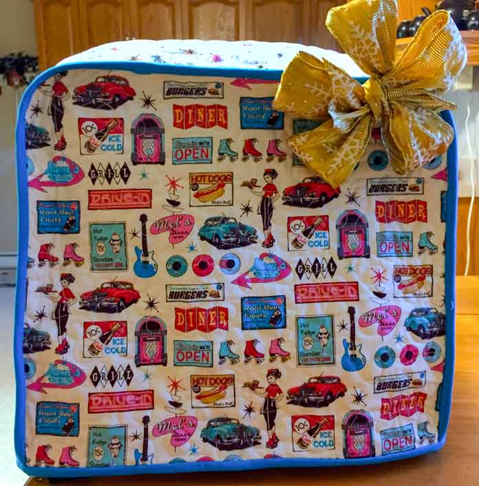Stand mixer cover ready for gift giving. Fabric by Northcott Mel's Diner and ColorWorks, Batting by Fairfield Quilters' 80/20.