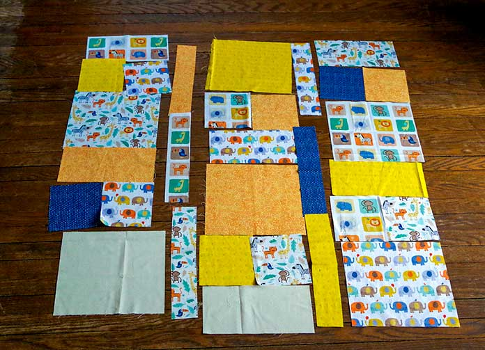 "This picture shows the animal print quilt completely cut and laid out ready to sew. You see 3 rows of blocks with the strips in between. Each block has (2) 5½"" squares, a 10½"" x 5½"" rectangle and a large 10½"" square; various squares and rectangles are arranged to create the quilt."