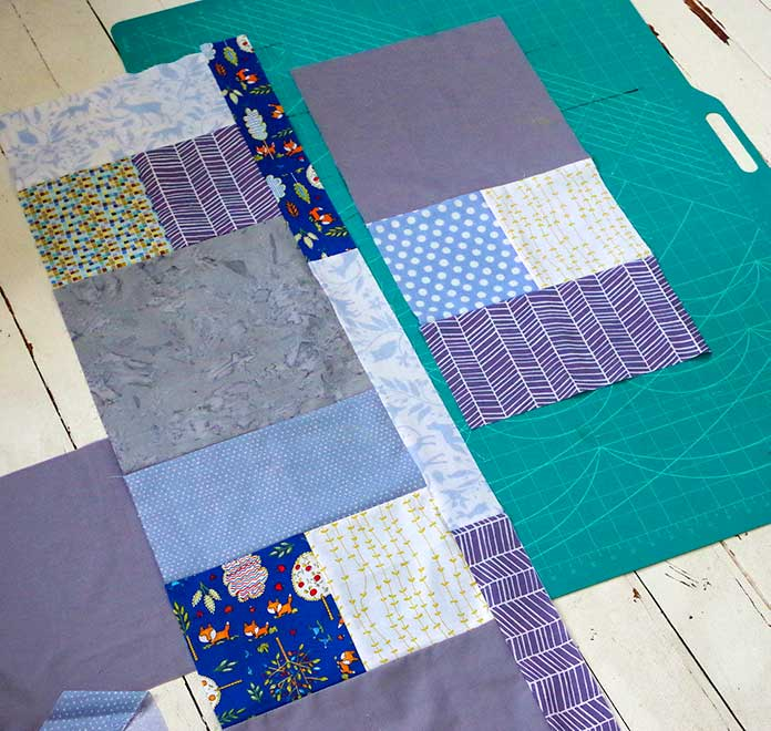 This picture shows the gray quilt blocks sewn together. You see two blocks sewn together with a strip on the right-hand side. Another quilt block has been assembled and is sitting to the right of the first third of the assembled quilt.