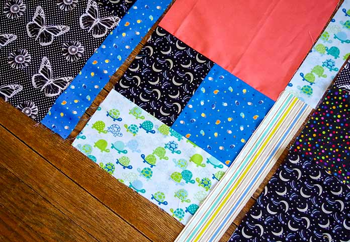 This is a picture of the turtle quilt being assembled. You can see the rectangular turtle block on the bottom that has been attached to the snails and moon blocks (these were sewn together first) and the larger salmon colored block is on top. The strips are visible but, not sewn on and the other blocks are on either side (butterflies and moons).