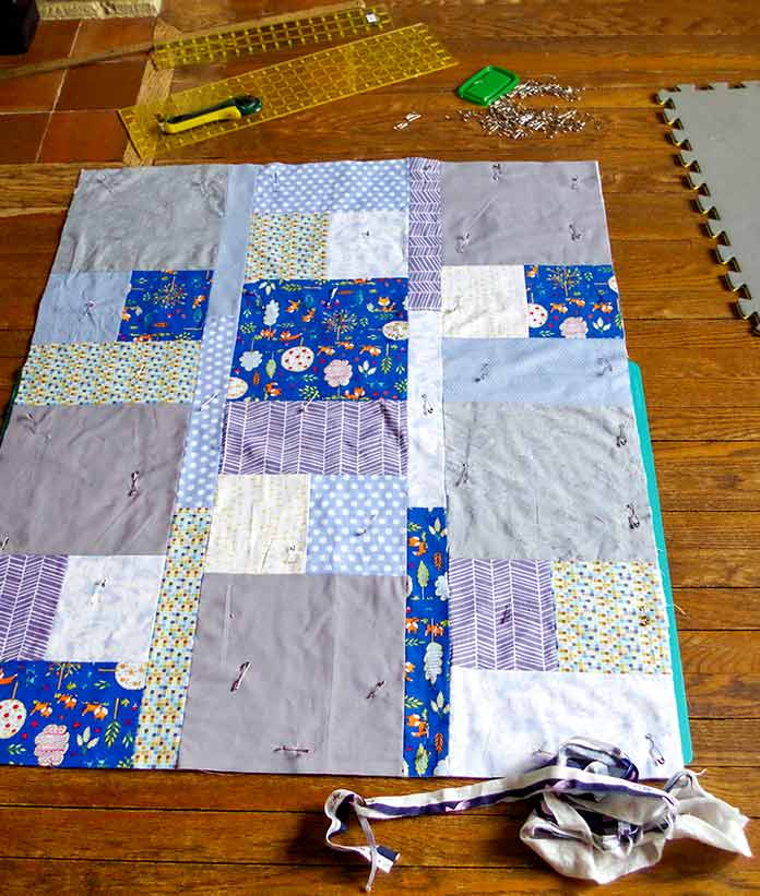 The quilt with gray tones is complete. It's pinned to the backing with the batting in between. You can see the pins spread out across the quilt ready for machine quilting. You can also see the rulers, cutter and pins on the floor in the background. In the foreground, you can see the scraps of the quilt that were cut off in order to square it. A green cutting mat is under the quilt and it was used to square the quilt.