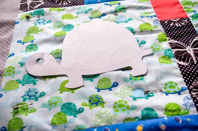 The paper pattern for the turtle shape is seen on the large square of light green and dark green, as well as bluish and white tones fabric. The fabric is the largest square and the turtle is waiting to be traced for machine quitting.