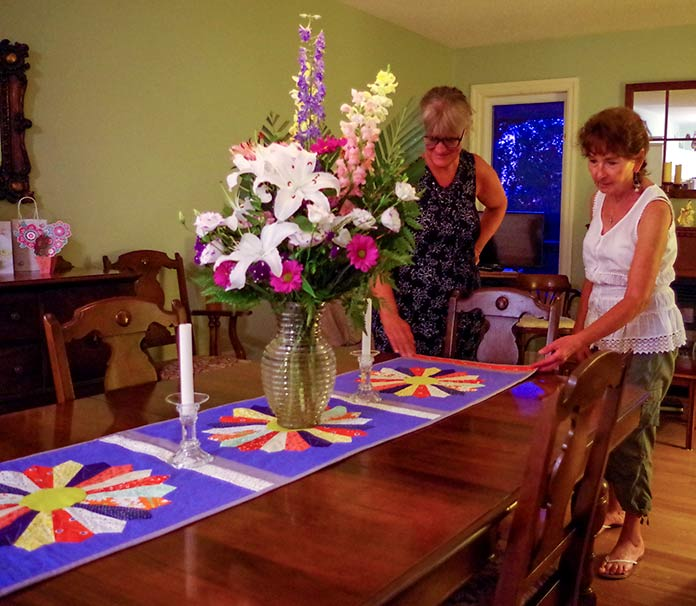 I am pictured here with my mentor and friend, Helen, at her table, showing the dresden plate table runner with the multicolored plates and blue backing.