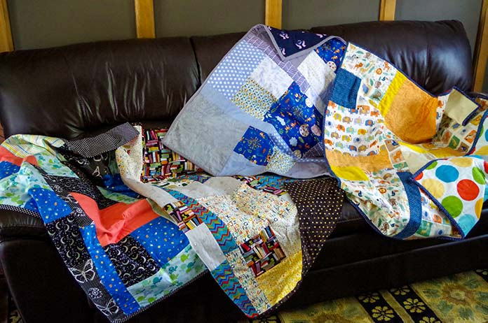 four completed quilts lying together, overlapping, showing the different colours and patterns.