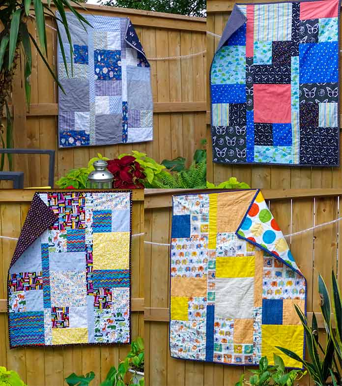 The four quilts are pictured hanging outside. The bunny quilt is in gray tones, the turtle quilt in black, orange and blue tones, the first elephant print has animal prints in yellow and orange tones and the final elephant quilt has zoo animals, schoolbooks and letters in brown and yellow tones.