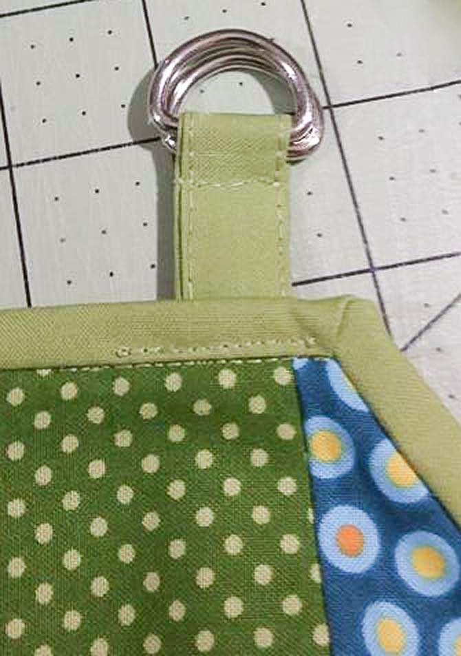 "The 4"" strap made with Northcott Colorworks solids and D-rings is attached to the neck line of the apron."