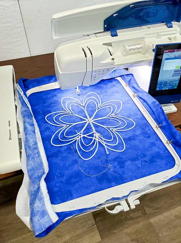 White thread on a blue background of a Yarn Couching embroidery design stitched in the DESIGNER Majestic Hoop using the Husqvarna Viking Designer Brilliance 80
