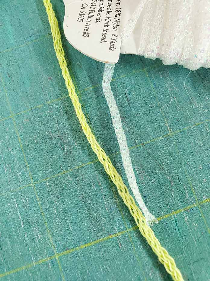 A round green yarn and a flat, white yarn for use with the Yarn Couching embroidery techniques