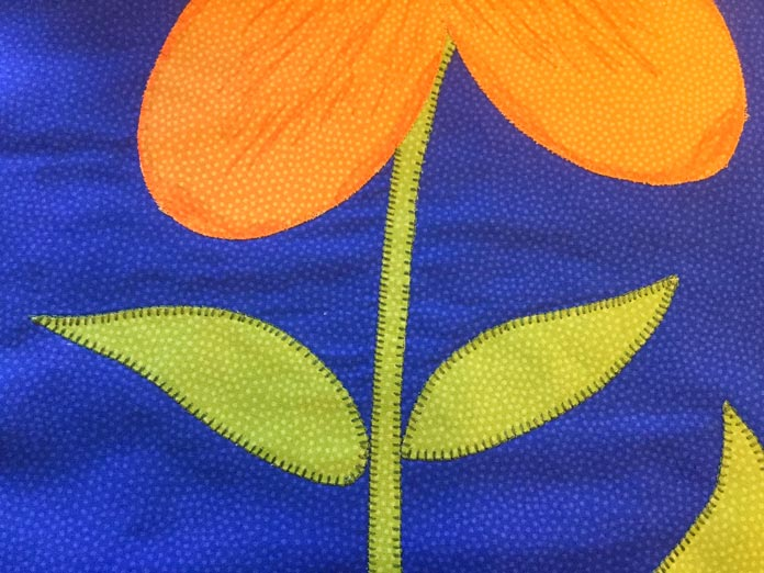 A blanket stitch was used to stitch the leaves and stems in place.