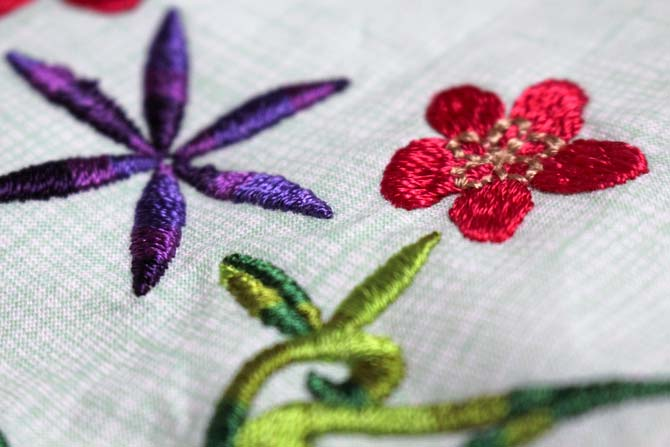 Purple and red flowers machine embroidered with solid and variegated Accent rayon thread from WonderFil.