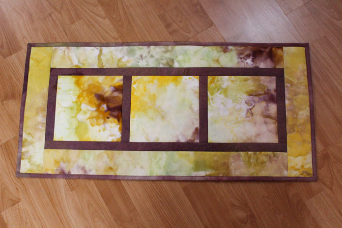 Hand dyed fabric blocks with narrow sashing and border create a quick and easy wallhanging.