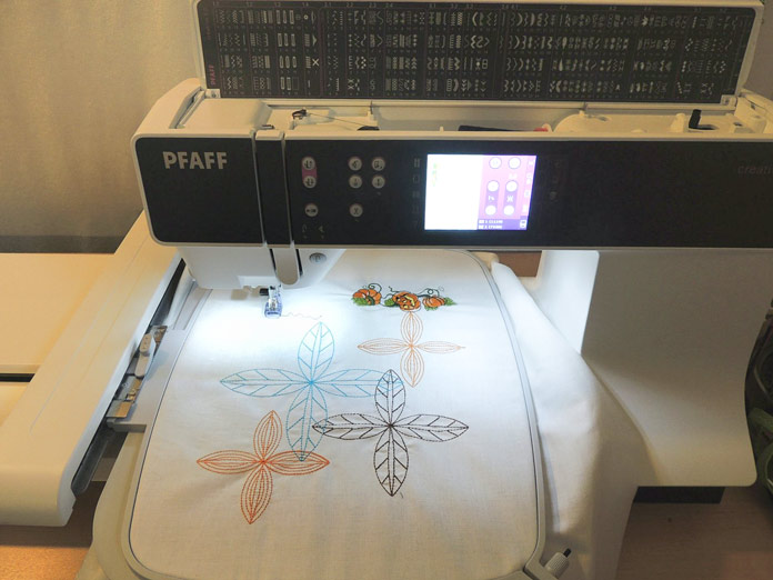 Stitching out the pumpkin embroidery design in top left corner of hoop