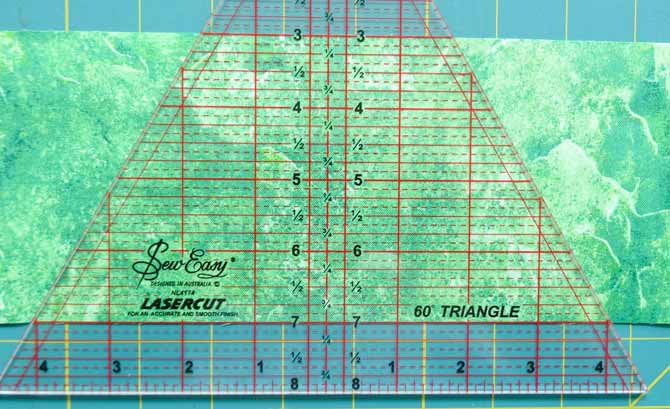 A triangle ruler is place on a strip of fabric. the ruler is taller than the strip of fabric, this will ensure that when the fabroic is cut it will create the tumbling block shape.