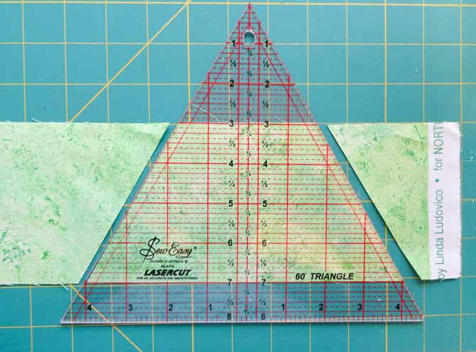 The Sew Easy Triangle ruler is placed on a strip of fabric as a guide to cut tumbling block shapes.