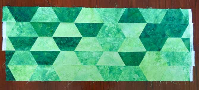 Rows of trapezoid shaped fabrics are sewn together to make tumbling blocks. The edges will be trimmed with the rest of the quilt is completed. This completes the 'grassy' part of this impressionistic quilt. Northcott Fabrics and Sew Easy Triangle Ruler make this possible.