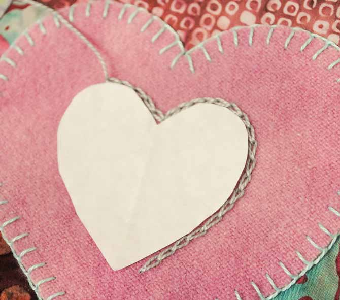 A freezer paper heart is used as a guide for chain stitching with Eleganza thread
