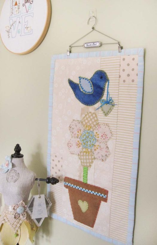 Mini quilted wall hanging with a blue bird on top of a potted flower. Stitched with WonderFil.