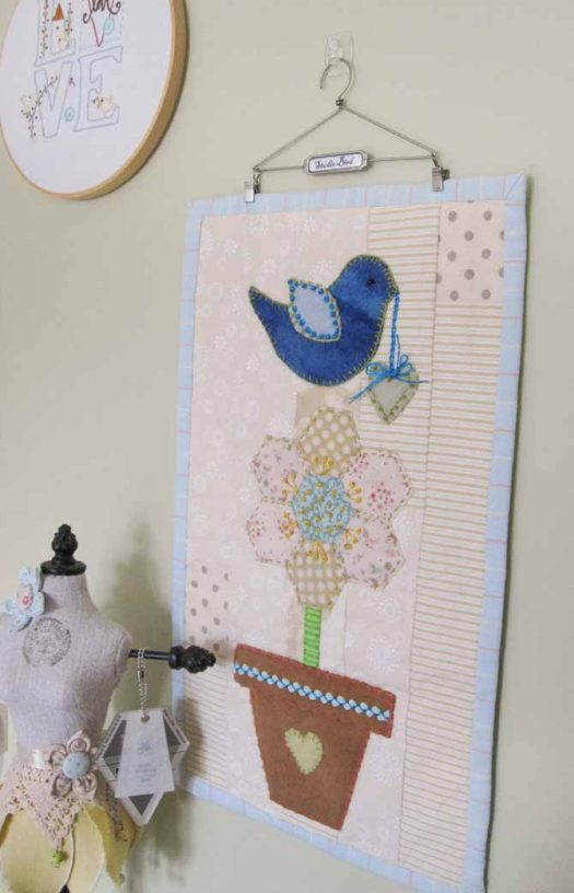 A hanger by Tim Holtz displays the studio bird mini quilt on a wall. WonderFil Specialty Threads.